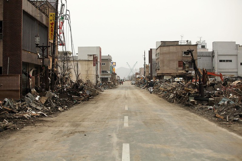 An urban road with ruined buildings on either side.