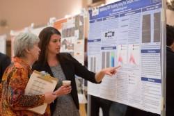 Kelly Regimbal shows her award-winning poster to  JSG Dean Sharon Mosher.