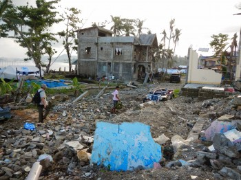 Typhoon Haiyan was the strongest hurricane ever recorded to make landfall. Working with villagers, the researchers sampled wells among the debris and destruction. Professor Phil Bennett is walking over the ruins of a concrete house. Image: Bayani Cardenas