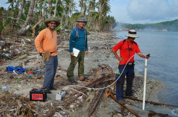 Filipino scientists Raymond Rodolfo and Hillel Cabria with Jackson School graduate student Peter Zamora (middle in blue) taking water samples from a piezometer. The data collected was used to help build a computer model that predicted how salt water moved through the sand to the aquifer