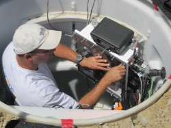 Engineer secures waterproof enclosure for seismic station electronics