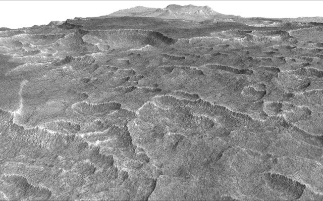 This vertically exaggerated view shows scalloped depressions in a part of Mars where such textures prompted researchers to check for buried ice, using ground-penetrating radar aboard NASA's Mars Reconnaissance Orbiter. They found about as much frozen water as the volume of Lake Superior. NASA/JPL-Caltech/University of Arizona