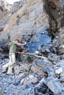 Robert Zinke (B.S. 2012) against a wall of obsidian at Long Valley Caldera in California.