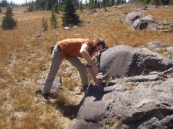 Tim Prather, then an undergraduate, chips stone samples from a lava flow in Yellowstone. He is now a graduate student at the Jackson School.