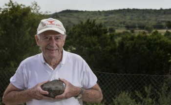 Leon Long, professor emeritus of geology at the University of Texas, holds a volcanic rock sample from the ancient volcano known as Pilot Knob seen in the background in Southeast Austin