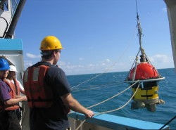 Team members deploy an ocean bottom seismometer.