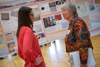 Jackson School Dean Sharon Mosher talks with second year master's student Casey O'Brien about her work on on deformation bands in the San Rafael Desert in Utah at the Student Research Symposium.