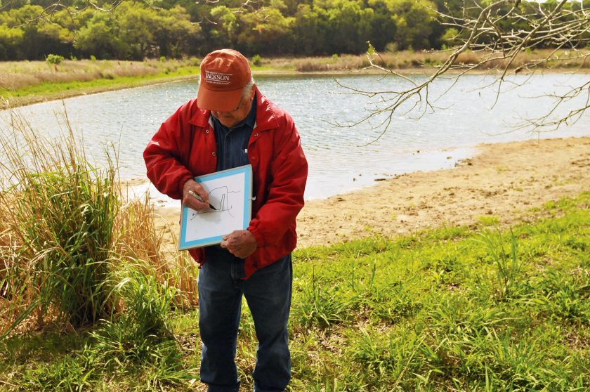 Leslie P. White explaining the hydrology of one of the ponds he built on the property.