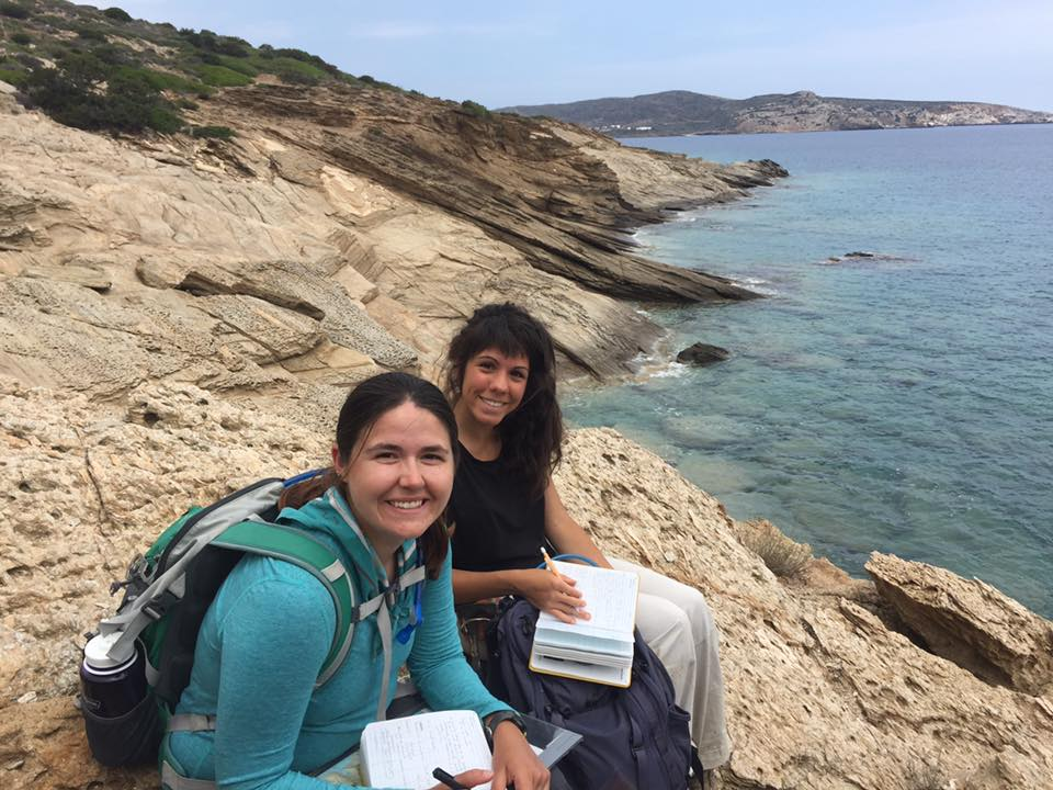 Figure 1. Eirini Poulaki (M.S. '18, back) and Megan Flansburg (M.S. '18, front) sitting on the Cycladic Blueschist Unit along the beach on a rare cloudy day, Ios Island, Greece (2017). Photo by Dr. Daniel Stockli.