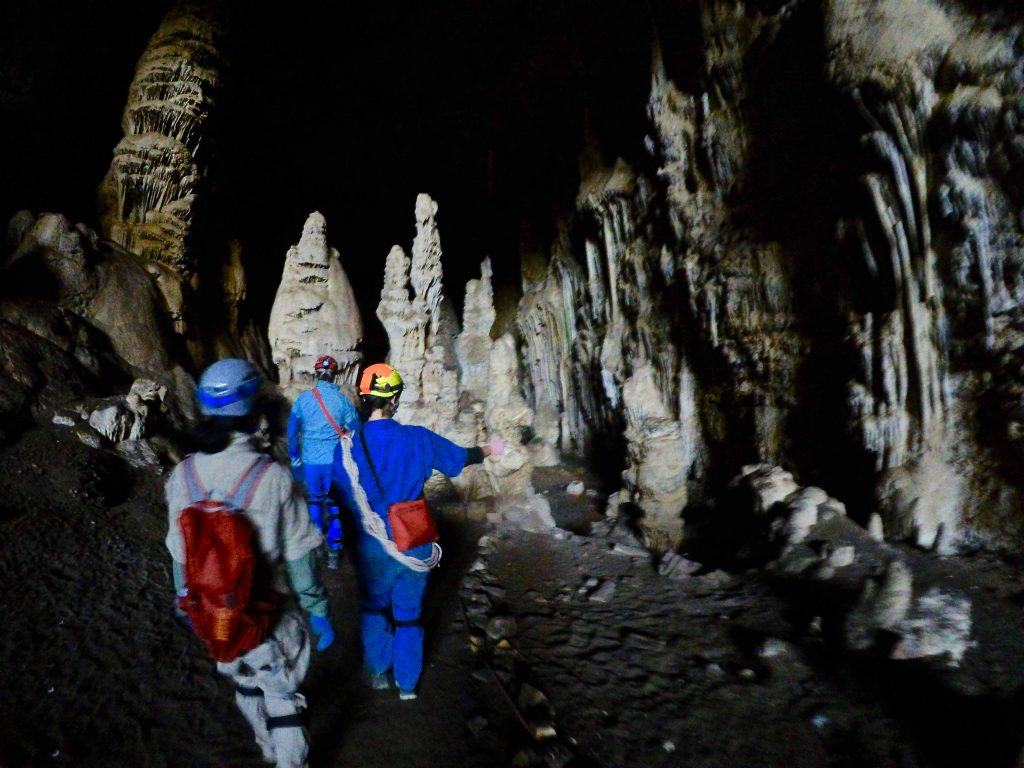 Natasha (front), Kara (middle), and our wild caving guide (back) walking through the first cave room (before dancing with wall to squeeze into small hole) (Photo Credit: Lakin Beal).